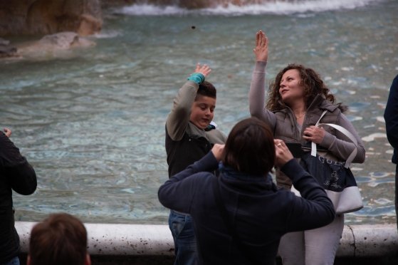 mom and son coin toss at Trevi Fountain