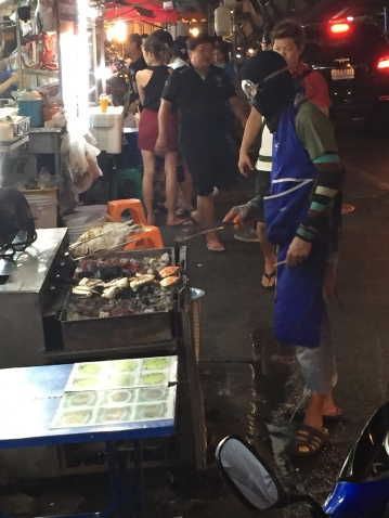 Cooking salt crusted fish along the street, Bangkok
